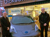 Dave and Calvin Gill standing next to the eco-friendly electric, Nissan Leaf